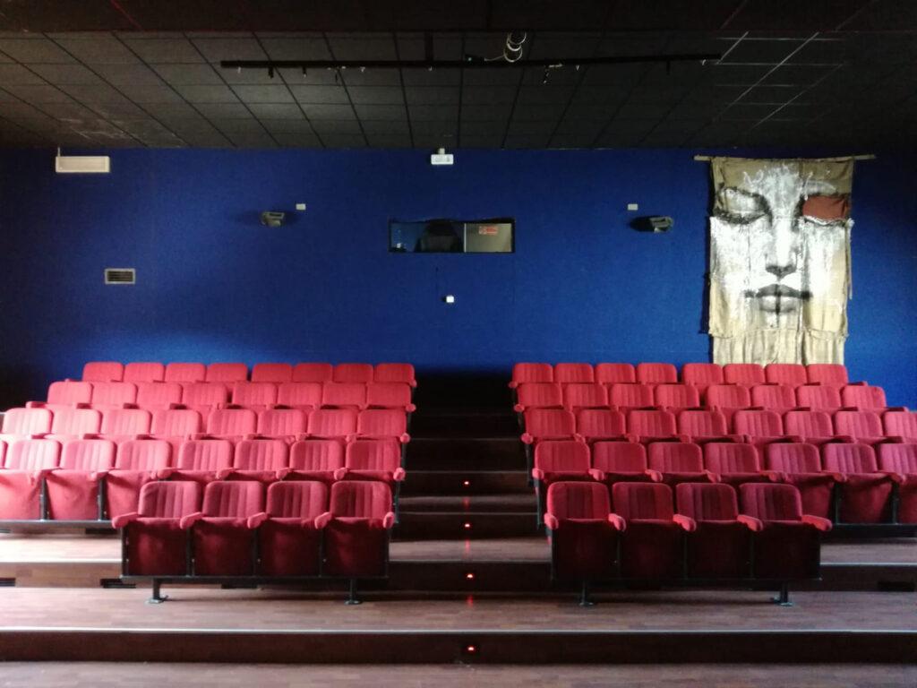 La sala cinema. 2014. Sullo sfondo un'opera di Max Gasparini, realizzata nell'aprile 2014 durante la performance Sono apparso alla Madonna Night.