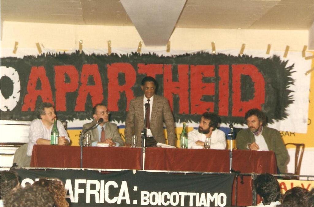 Incontro Stop Apartheid, con la partecipazione di Benny Nato, rappresentante in Italia dell'African National Congress; nella rassegna anche il concerto di The Gang. 1988.